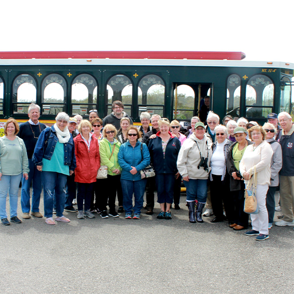 A large group of people standing outside with the cape may mac trolley behind them