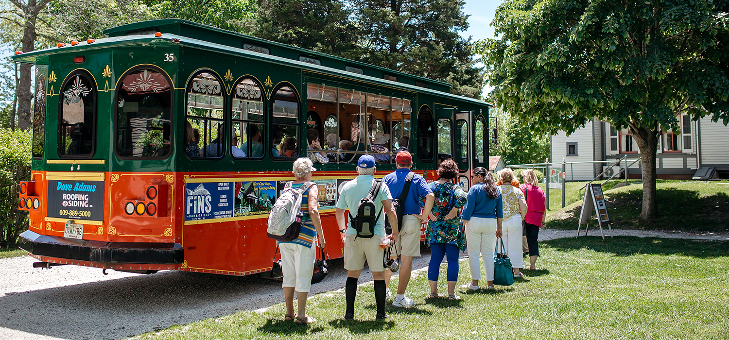 Group of people in line to walk onto the cape may mac red and white trolley for a tour