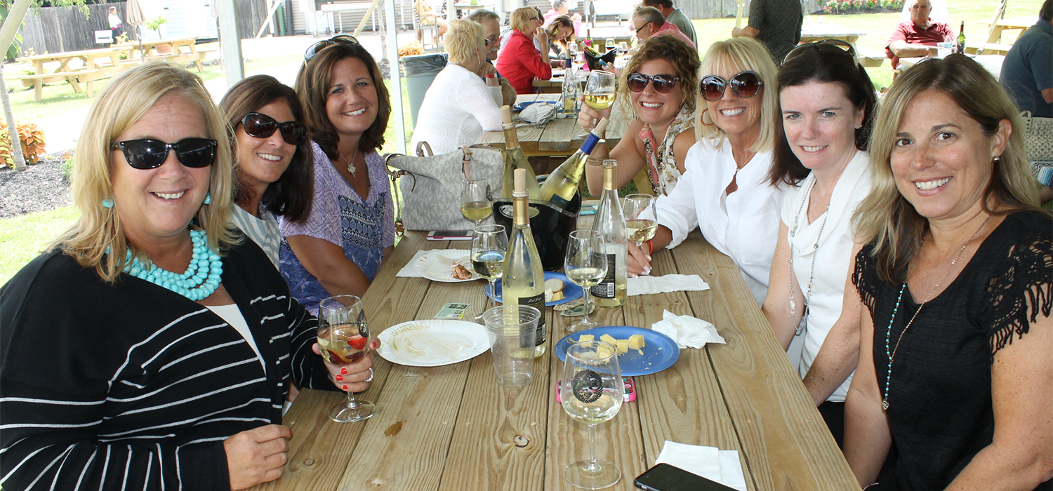 A group of women at a winery sitting at picnic table with wine glasses and cheese plates