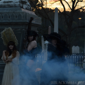 3 actors dress in gothic attire posing in a cemetery with a cloud of fog rolling in