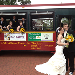bride and groom posing besides a cape may green and red trolley. Bridal party are leaning out the windows.