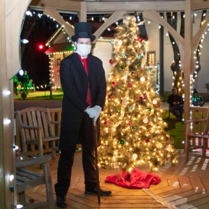 Dr. Physick standing outside by a lit Christmas tree.