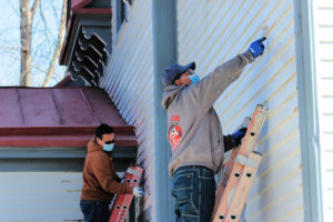 two men repainting a building