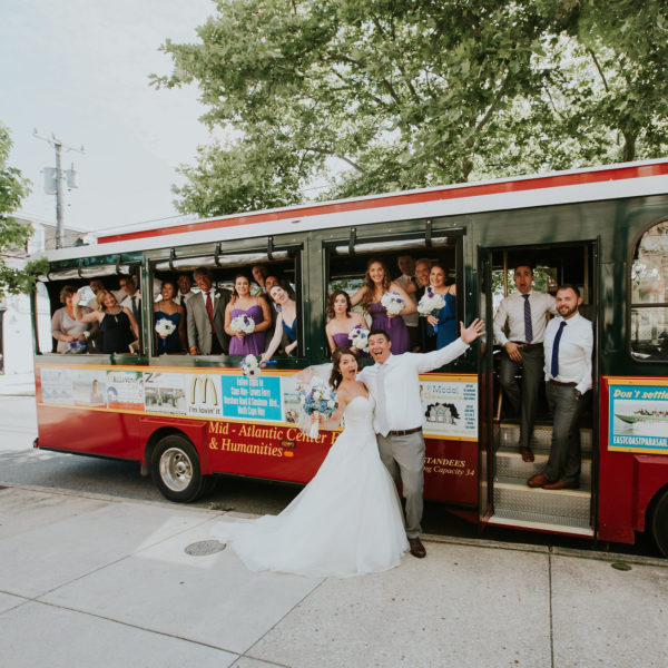 Wedding party posing in front of a red trolley