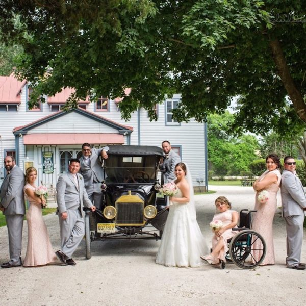 wedding group posing on a Victorian estate with a Model T car
