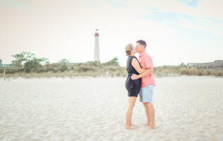 man and woman kissing on the beach with lighthouse in the background